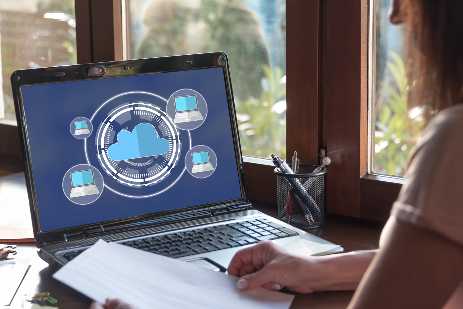 woman using a laptop computer with rendering of computer icons and cloud infrustructure