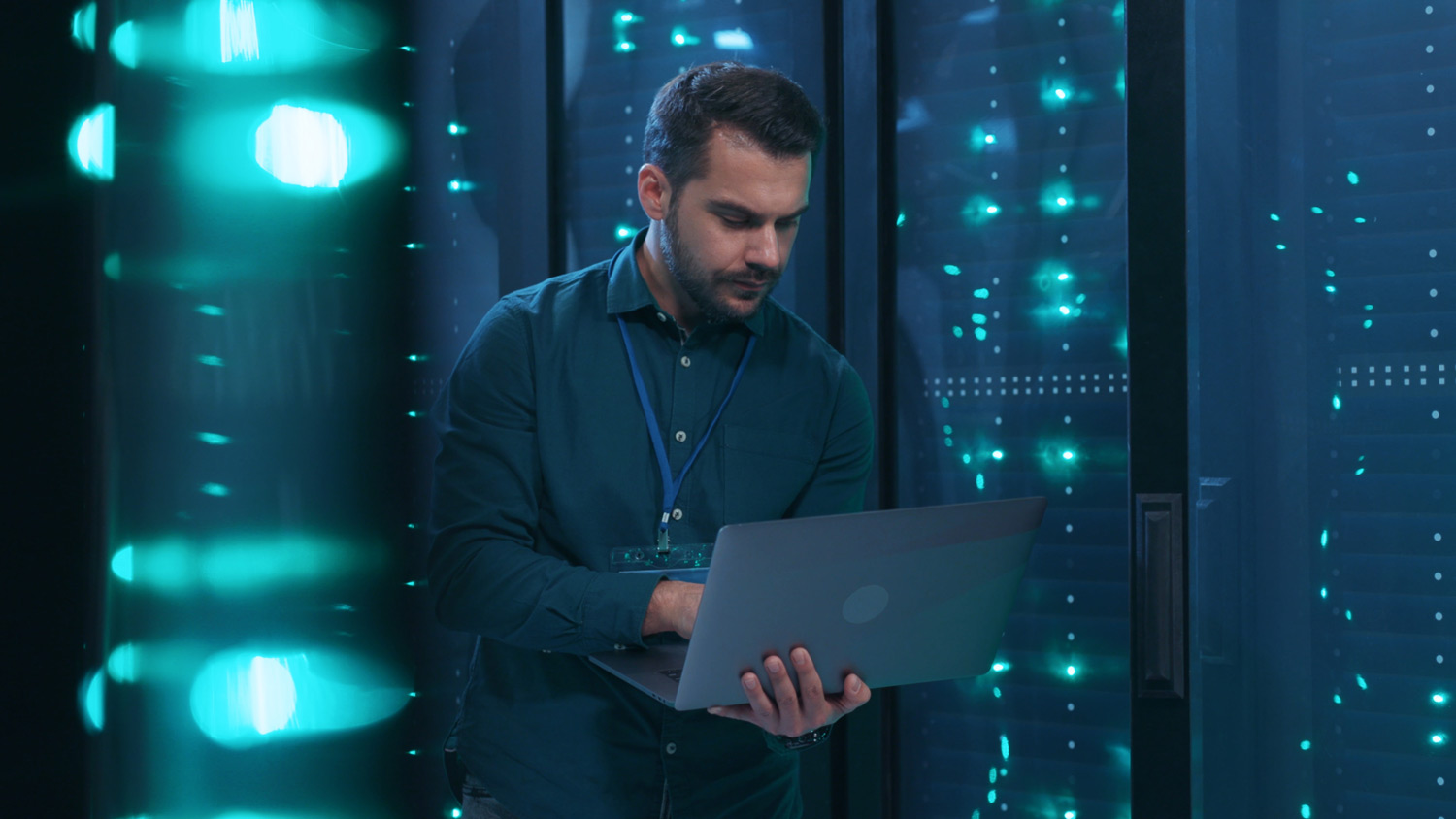 male technician using laptop with server racks in background representing Data Recovery & Backup