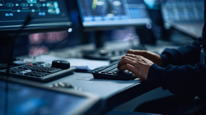 man's hands on keyboard with computer screens in background - Managed IT Services